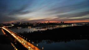 Aftonstad med en bro och en flod royaltyfria foton
