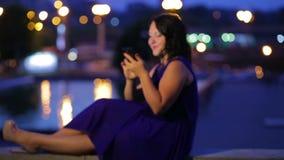 Aftontid sitter en ung kvinna i en blå klänning på en ångare i gatan som läser ett meddelande i smartphonele och dre lager videofilmer
