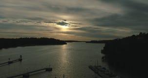 Aftontimelapseskott av en fjärd i Stockholm, orange solpiercing till och med moln stock video