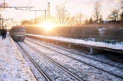 Aftonvinterlandskap med järnvägsstationen Arkivbild