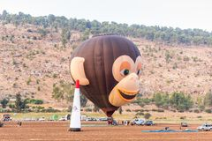Pilots of air hot balloon in the shape of head of a monkey are preparing to fly out at the festival of air hot balloons. Afula, Israel, 3 August, 2018 : Pilots stock photography