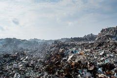 Afval bij het hoogtepunt van de huisvuilstortplaats van rook, draagstoel, plastic flessen, vuilnis en afval bij tropisch eiland royalty-vrije stock afbeelding