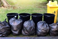 Afval, huisvuil in zwarte zak en bak, stapel van de troepvuil van het bakafval en vuilniszak velen in tuin openbaar park, plastic Stock Afbeelding