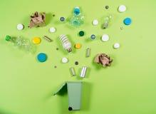 Afvalbakken en geassorteerd die huisvuil op groene, kringloopconce worden geïsoleerd stock fotografie