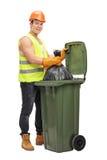 Afvalcollector die een huisvuilbak leegmaken Royalty-vrije Stock Afbeelding
