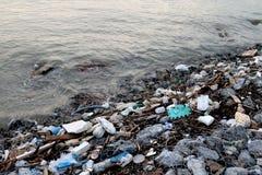 Afvalkust, Huisvuil op strandverontreiniging, Afvalafval in rivier, Giftig afval, Afvalwater, Vuil water in rivier stock afbeelding