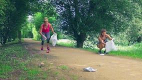 Afvalstapel en twee meisjes die het plogging doen stock video