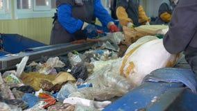 Afvaltransportband Arbeidershanden bij transportband sorterend huisvuil bij een recyclingsinstallatie stock video