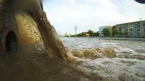Afvalwater aan stadskanaal Industriële pijp die vloeibaar afval lossen stock footage