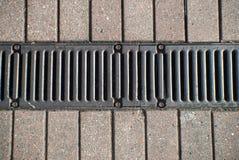 Afvoerkanaal in het midden van een bedekt voetpad Stock Afbeelding