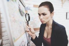 Agência de detetive privado A mulher está olhando o mapa do indício com a lupa no escritório foto de stock royalty free