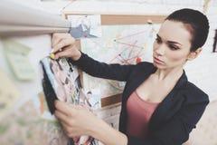 Agência de detetive privado A mulher está pondo fotos sobre o mapa do indício no escritório imagens de stock