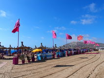 Red flags on beach in travel Agadir city in Morocco. AGADIR, MOROCCO EUROPE on FEBRUARY 2017: Red flags on beach in travel city with clear blue sky in warm sunny Stock Photography