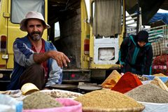 local man selling spices and grains at the market stock photo