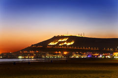 Agadir by night. Morocco. Agadir. General view of a tourist resort with the old kasbah on the top of hill. Seen illuminated sign in arabic God, King, Country on Stock Photos