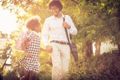 Again school. African American father and his daughter walking trough park royalty free stock photos