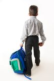Again to school. Back of schoolboy holding backpack and apple while going to school Royalty Free Stock Photography