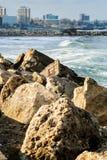 Agains de piedra de la presa el mar ondulado y la ciudad Imagen de archivo libre de regalías