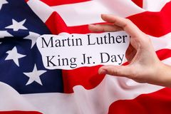 Against the American flag, the hand holding a sign with the inscription Martin Luther King Jr. Day. royalty free stock photo