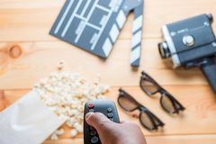 Against the backdrop of the film industry objects the remote fro. M the TV in the female hand stock image
