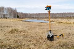 Against the backdrop of the lake and the field there are staked shovel in the ground on the shovel metal detector, wounding the sp. Against the backdrop of the stock image