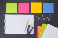 Against the background of a black Board with the inscription school, are subjects for study, colorful stickers, notebook, books,. Stapler and pencil royalty free stock photos