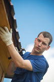Against the background of the blue sky master repairing roof royalty free stock images