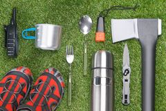 Against the background of a green lawn, lie a set of objects of the traveler, an ax, a walkie talkie, a folding knife, a fork, a. Spoon, a flashlight, a mug, a stock image