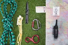 Against the background of a green lawn, there is a set of items for the expedition, a climbing rope, a map of the area, tourist. Matches and a walkie-talkie stock images