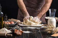 Against the background of men`s hands knead the dough. Ingredients for cooking flour products or dough bread, muffins Royalty Free Stock Photography