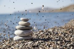 Against the background of the sea a pyramid of stones. And in the background small pebbles in the form of rain Royalty Free Stock Photo