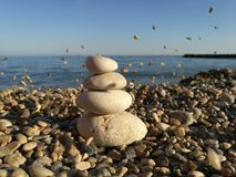 Against the background of the sea   pyramid of stones. In the evening light Stock Photos