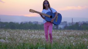 Against background of the urban landscape funny little girl musician on sunglasses playing the guitar and walks in meadow of dande stock video footage