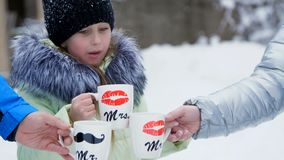 Against the background of winter forest, a girl of seven years drinks tea from a cup, on the cups, sponges are drawn.  stock footage