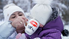 Against the background of the winter forest, a young woman, Mom gives a drink to a one-year-old daughter from a cup. They are dressed in funny hats with bumbon stock footage