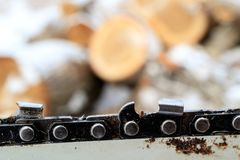 Against a background of wooden choks chainsaw chain close-up with signs of wear, the chain of which worked sawed firewood Stock Photography