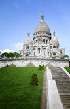Against blue sky and green field sunny day, The Basilica of Sacre Coeur at Montmartre in Paris, France Stock Images