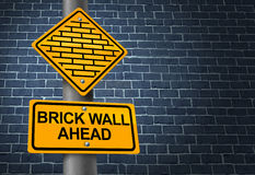 Against A Brick Wall. Business concept of hardship and difficult restrictions faced on a journey focused on success represented by a yellow traffic sign warning Royalty Free Stock Photos