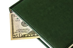 Against a light background lies a diary and part of a 50 dollar Stock Photography