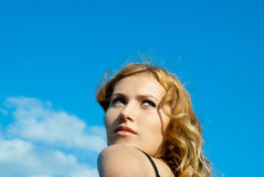 Against the sky-a beautiful red-haired girl Stock Images