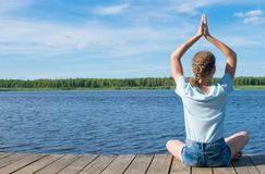 Against the sky, the girl sitting on the pier, doing yoga, outdoors royalty free stock images