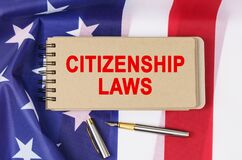 Free Against The Background Of The Flag Of The USA Lies A Notebook With The Inscription - CITIZENSHIP LAWS Royalty Free Stock Photo - 215041515
