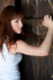 Against the wall. Strong fierce young woman standing against the old doorway royalty free stock photo