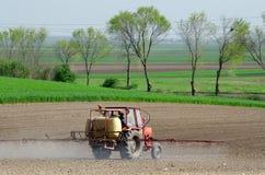 Againt för traktorbestänkandebekämpningsmedel buggar på plogat land på sunn Royaltyfri Fotografi