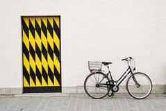 Againtst da bicicleta da cidade uma parede grande com porta Fotografia de Stock