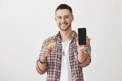 Agarre seu cartão de crédito e compre este telefone Retrato do homem novo satisfeito bonito com cerda e eyewear, puxando foto de stock