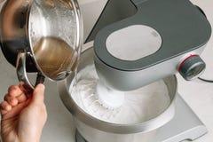 Agarsockersirap hälls in i piskade äggvitor med socker Processen av att göra marshmallowmarshmallowen i bakelseköket arkivfoton