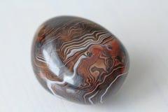 agata 与镶边纹理或样式的自然圆或卵形石玛瑙 一块美丽的石头是玛瑙 免版税库存照片