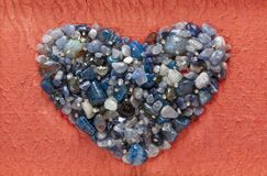 Agate blue crystals heart shape  closeup on elegant orange background