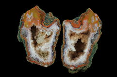 Agate. A cross section of the agate stone. Multicolored silica rings colored with metal oxides are visible. Inside geode is a `calcite brush` with goethite Stock Images